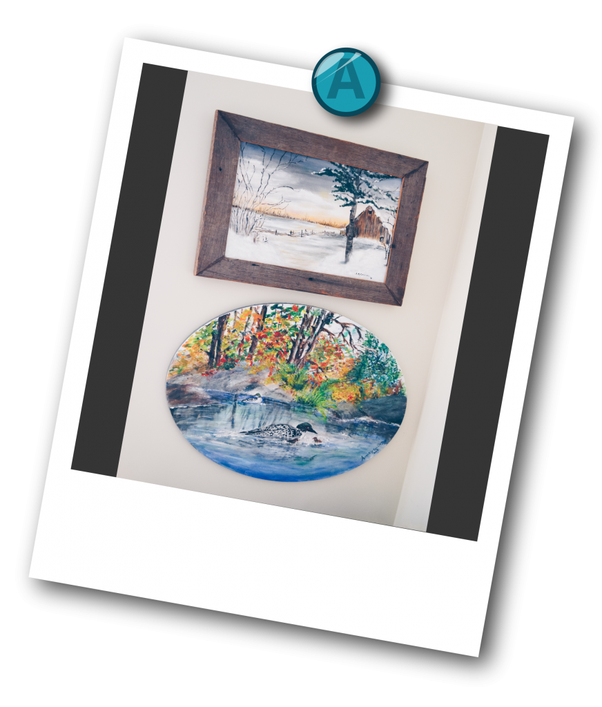 Two paintings hanging on the wall. One depicts a barn landscape during the winter, and the other is a loon in a lake with colourful trees in the background.